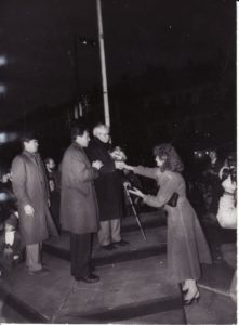 Tautinės vėliavos iškėlimas Panevėžyje, prie dramos teatro (1988 m. spalio 21 d.). Vėliavą iškėlė Juozas Miltinis – Panevėžio miesto Garbės pilietis. Gėles jam teikia kultūros skyriaus vedėja Rita Pribušauskienė. Šalia J. Miltinio – aktorius Algirdas Paulavičius, už jo – Faustas Keršys. PAVB FJM-841