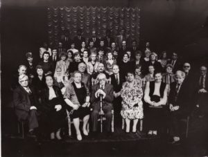 """Juozas Miltinis (centre) su Panevėžio dramos teatro aktoriais (buvusiais ir esamais) ir kitais teatro kolektyvo nariais, minint pirmojo spektaklio N. Pogodino """"Sidabrinis slėnis"""" pastatymo 50-metį. PAVB FJM-898/1"""