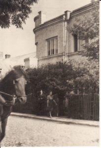 """Prie pastato P. Puzino g. Nr. 13. Keletą metų čia buvo aktorių bendrabutis, taip vadinamas """"Kolchozas"""". Šiame name su sodeliu šešis metus gyveno ne tik aktoriai, bet ir jų mokytojas Juozas Miltinis. Apie 1941–1943 m. Fotogr. Kazimiero Vitkaus. PAVB FKV-283/2"""