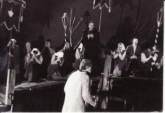 """Romas Gudaitis """"Atversk, angele, laiko knygą"""" (rež. J. Dautartas), 1984 m. Scena iš spektaklio. Viduryje Rudolfas Jansonas - Klebonas. Fotogr. K. Vitkaus. PAVB FKV-242/1-16"""