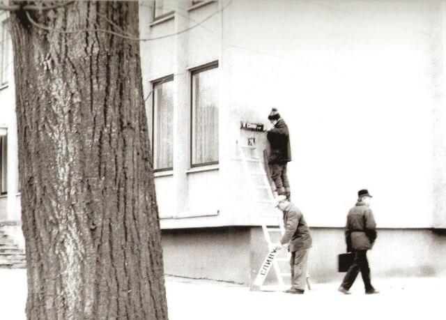 """Nuimami R. Čarno gatvės užrašai, grąžinus gatvei Vasario 16-osios pavadinimą. 1989 m. Nuotrauka iš fotografijų albumo """"Sąjūdis Panevėžyje"""" (2008)"""