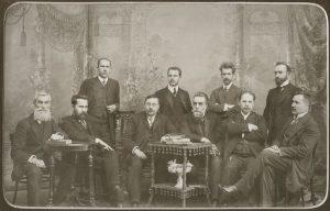 Lietuvių mokslo draugijos komitetas. Sėdi iš kairės: Juozas Kairiūkštis, Antanas Smetona, Augustas Niemi, Jonas Basanavičius, Antanas Vileišis ir Jonas Vileišis. Stovi iš kairės: Juozas Balčikonis, Zigmas Žemaitis, Mykolas Biržiška, Jurgis Šlapelis. Marijos ir Jurgio Šlapelių namas-muziejus. Nežinomas fotografas. 1911–1912 m. Iš: https://www.limis.lt/greita-paieska/perziura/-/exhibit/preview/69558639?s_id=HOGWQBDGaTB0gWdE&s_ind=17&valuable_type=EKSPONATAS