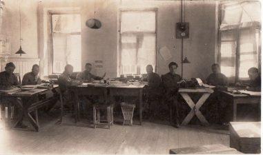 Ketvirtojo pėstininkų Lietuvos karaliaus Mindaugo pulko štabo tarnautojai darbo vietose. Prie spausdinimo mašinėlės sėdi Julius Ivanovas. 1925 07 17. PKM GEK 22087