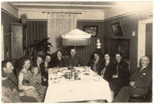 Svečiuose pas I pėstininkų divizijos štabo adjutanto kapitono Juozo Rinkevičiaus šeimą. Sėdi gale stalo centre karininkas Juozas Rinkevičius su žmona, 1-as iš kairės – leitenantas Vladas Aižinas su žmona Ona Kazokaite-Aižiniene ir vaikais. Panevėžys, 1932 05 08. PAVB F8-88
