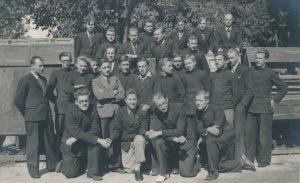 """Ukmergės valstybinės mokytojų seminarijos moksleivių grupė. Su įrašu nuotraukos reverse: """"1938 m. rugsėjo mėn. pradėjus mokytis Ukmergės valstybinėje mokytojų seminarijoje"""". Stovi iš kairės 3-ias (šviesiu švarku) Stasys Šneideris. Ukmergė. 1938 m. PAVB F51-59"""