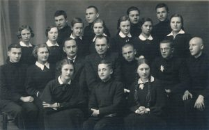 """Biržų, Pasvalio ir Panevėžio moksleiviai – """"Meno kuopos"""" organizuoto literatūros vakaro Panevėžyje dalyviai. 1-oje eilėje iš kairės: 1-a Adelė Karvelytė, 2-as Panevėžio moksleivių literatų būrelio """"Meno kuopa"""" pirm. Stasys Šneideris, 3-ia Pranė Aukštikalnytė (vėliau Jokimaitienė). 2-oje eilėje iš kairės: 1-as Eugenijus Matuzevičius, 2-a Kazimiera Federauskaitė, Panevėžio valstybinės gimnazijos mokytojai, """"Meno kuopos"""" globėjai Petras Rapšys ir Petras Juodelis, 5-as Paulius Drevinis, 6-as Julius Šimkevičius, 7-as Bronius Krivickas. Viršutinėje eilėje iš kairės 2-as Aleksandras Petkevičius, 4-as Vytautas Stukas. Fotogr. J. Žitkaus. 1937 m. PAVB F70-783"""