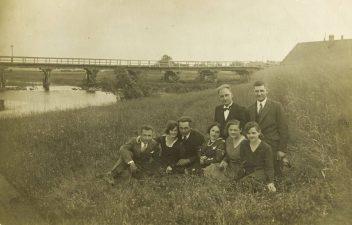6. Tiltas per Nemunėlio upę ties Kvetkų miesteliu. Pievoje prie upės sėdi grupelė žmonių: Baranauskas iš Kvetkų, mokytojas Balbierius iš Latygalos, malūnininkas N. Tarulis, Gaigalų mokyklos mokytojai, Kvetkų miestelio mokytoja A. Zarankaitė, Latygalos mokytoja Balbierienė. 1934 06 13