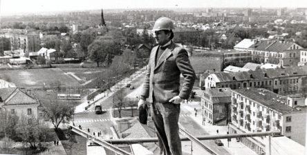 PST Specializuotos apdailos darbų valdybos Nr. 5 vyr. mechanikas Romualdas Palionis ant statomo 13-os aukštų daugiabučio Panevėžyje, Vilniaus ir Basanavičiaus gatvių kampe, stogo. Apie 1979 m.