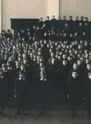 Panevėžio lenkų gimnazijos moksleiviai ir pedagogai gimnazijos salėje. Dešinėje stovi gimnazijos direktorius I. Pereščakas. Fotoateljė J. Žitkaus ir J. Pauros. Panevėžys. 1933 m. PAVB F96-183