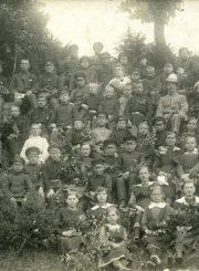 """Anykščių vidurinės mokyklos mokiniai ir mokytojai ekskursijoje. E. Šukytė-Juzulėnienė sėdi 1-a iš dešinės. Kt. nuotraukos pusėje įrašas: """"Anykščių vidurinės mokyklos ekskursijos Puntuko laukuose prie vieškelio. Šitos fotografijos savininkas Jonas Šukys. 1921 m."""" PAVB F116-58"""