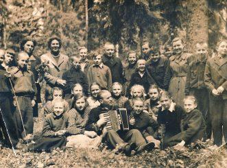 Panevėžio II septynmetės mokyklos 6 klasės išvyka į Dembavos pušynėlį mokslo metų pabaigoje. 1-oje eilėje sėdi su akordeonu muzikos mokytojas Vladas Indrikonis, 3-ioje eilėje iš dešinės 3-ia klasės auklėtoja Birutė Palaimaitė, 8-as direktorius Jokūbas Skiauteris. 1958 m.