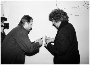 """Stasys piešia piešinį """"Algimanto galerijoje"""". Šalia – menininkas Stasys Petrauskas. Panevėžys, 1995 m."""