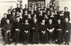 Panevėžio gimnazistai ateitininkai su dvasios vadovais kun. Alfonsu Sušinsku (2-as iš dešinės), kun. Povilu Šidlausku (centre) ir kun. Adolfu Stašiu (sėdi 2-as iš kairės). 3-ioje eilėje iš dešinės 2-as Jonas Stasiūnas, 3-ia Ona Kiaulėnaitė. Fotogr. J. Žitkaus. 1938 m. Panevėžio kraštotyros muziejus, PKM 21922 F4693