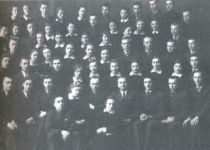 """Panevėžio moksleivių literatų būrelio """"Meno kuopa"""" nariai su kuopos globėjais mokytojais Petru Juodeliu ir Mykolu Karku. 2-oje eilėje sėdi iš kairės: 1-as pirm. Aleksandras Petkevičius, 2-as Julius Šimkevičius, 3-ias Bronius Stasiukaitis, 4-a Marija Slavinskaitė, 5-as mokytojas Petras Juodelis, 6-as mokytojas Mykolas Karka, 7-as Jonas Stasiūnas, 8-as Algirdas Kuzma, 9-as A. Maulis; 3-ioje eilėje dešinėje: Kazimieras Naruševičius. Panevėžys. Apie 1938-1939 m. (Nuotrauka iš kn.: Panevėžio Juozo Balčikonio gimnazija prisiminimuose. Panevėžys. 2007. P. 411)"""
