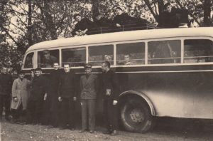 Panevėžio valstybinės gimnazijos moksleiviai kraštotyrininkai prie autobuso, prieš išvykdami rinkti senienų. Iš kairės 4-as – Jonas Stasiūnas, 5-as – Vytautas Petkevičius, dešinėje Aleksandras Petkevičius; pro langą žiūri Grinkevičius. 1938 m. Panevėžio kraštotyros muziejus, PKM 23473 F5395