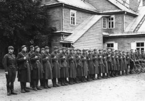Panevėžio valstybinės gimnazijos moksleiviai – kariuomenės manevrų dalyviai gimnazijos kieme. 1-oje eilėje iš kairės 14-as – Jonas Stasiūnas. Apie 1939 m. Aušros Stasiūnaitės asmeninis fotografijų archyvas
