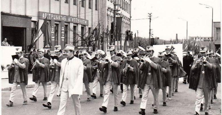 """Panevėžio """"Ekrano"""" gamyklos pučiamųjų instrumentų orkestras sovietinėje demonstracijoje. Priekyje – orkestro vadovas Donatas Baltrūnas. XX a. 8 deš. Nuotrauka iš Panevėžio kraštotyros muziejaus rinkinių"""