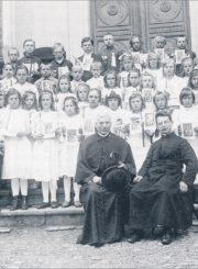 Vaikų Pirmoji Komunija Panevėžio Šv. apaštalų Petro ir Povilo bažnyčioje. Priekyje sėdi: kun. Juozapas Gražys ir Antanas Juška. Stovi 1-oje eilėje iš kairės 2-as Kazimieras Naruševičius. 1931 m. // Čiplytė, Joana Viga. Kazys Naruševičius: tapytojas, mokytojas. Vilnius, 1999. P. 11
