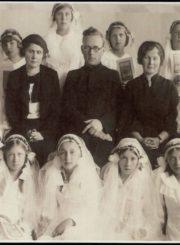 Panevėžio mergaičių gimnazijos moksleivių Pirmosios komunijos šventė. 2-oje eilėje iš kairės: 2-a gimnazijos direktorė Marija Giedraitienė, 3-ias kapelionas kunigas Adolfas Stašys, 4-a mokytoja Marija Januškevičienė. Panevėžys. 1936 m. Panevėžio apskrities Gabrielės Petkevičaitės-Bitės viešoji biblioteka, Almonijos Marcinkevičiūtės-Bernadišienės fondas F92-111