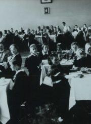 Panevėžio mergaičių gimnazijos 1937 m. abiturienčių išleistuvių vakaras. Kairėje, prie 2-ojo staliuko sėdi pedagogai: Jurgis Elisonas, dir. Marija Giedraitienė, kun. Adolfas Stašys, Oskaras Liudvigas. 1937.06.19. Panevėžio apskrities Gabrielės Petkevičaitės-Bitės viešoji biblioteka, Marijos Giedraitienės fondas F106-54