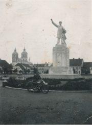 """Mokytojas Bronislovas Žiaunys, motociklu atvykęs į Kudirkos naumiestį ir įsiamžinęs prie paminklo rašytojui, tautinio atgimimo skleidėjui, """"Varpo"""" redaktoriui dr. Vincui Kudirkai (paminklo aut. skulpt. V. Grybas). Kudirkos Naumiestis. 1937 m. Panevėžio apskrities Gabrielės Petkevičaitės-Bitės viešoji biblioteka, Vytauto ir Silvijos Vilkončių fondas F154-244"""