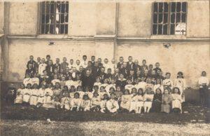 Vaikų Pirmoji Komunija. Centre sėdi vikaras Povilas Šidlauskas. Šventės dalyviai įsiamžinę prie I-ojo pasaulinio karo metais apgriautos Tauragės Švč. Trejybės bažnyčios. 1919 m. Nuotrauka iš Kristupo Šidlausko asmeninio archyvo