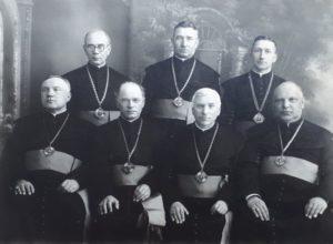 Panevėžio vyskupijos kunigai – kanauninkai. Iš kairės: kan. Ignas Labanauskas, kan. Pranciškus Strakšas, kan. Juozapas Gražys, kan. Jonas Maciejauskas. 2-oje eilėje iš kairės: kan. Mykolas Karosas, kan. Petras Strelčiūnas, kan. Povilas Šidlauskas. Panevėžys. XX a. 3 deš. pab. – 4 deš. pr. Nuotrauka iš Kristupo Šidlausko asmeninio archyvo