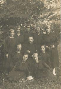 """Jurbarko """"Saulės"""" progimnazijos kapelionas kunigas Povilas Šidlauskas su gimnazistėmis. Apie 1923 m. Nuotrauka iš Kristupo Šidlausko asmeninio archyvo"""