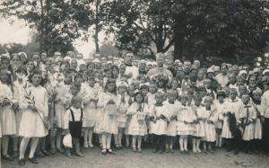Biržuose su vaikais, priėmusiais Pirmąją komuniją. Iš kairės: kun. Jonas Nagulevičius, vysk. Kazimieras Paltarokas, kun. Povilas Šidlauskas. Fotogr. P. Ločerio. 1934 m. Nuotrauka iš Panevėžio vyskupijos kurijos archyvo