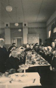 Šv. Vincento Pauliečio draugijos Panevėžio skyriaus organizuotos vaišės vargšams šv. Velykų proga. Kairėje: Draugijos valdybos pirmininkas kan. Povilas Šidlauskas. Panevėžys. 1936 m. Nuotrauka iš Kristupo Šidlausko asmeninio archyvo