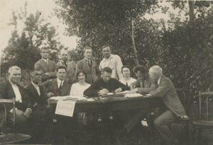 """Jurbarko """"Saulės"""" progimnazijos mokytojai. Iš kairės: 1-as Jurgis Steponaitis, 3-ias Kleopas Matusevičius, 4-a Ona Geniušienė, 5-as kapelionas kun. Povilas Šidlauskas (rašo), (?), 7-as dir. Antanas Giedraitis-Giedrius (skaito), 8-as Albertas Šileris. 2-oje eil. stovi iš kairės : 1-as Juozas Giedraitis, 2-as Jonas Pocius, 3-ias Antanas Šarkauskas (?), 4-as Juozas Kasiulaitis. Apie 1923 m. Nuotrauka iš Kristupo Šidlausko asmeninio archyvo"""
