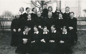 Panevėžietės moksleivės ateitininkės su dvasininkais. 2-oje eilėje iš kairės: 1-as kun. Bronislovas Jareckas, 3-ias kun. Adolfas Stašys, 4-as: kun. Povilas Šidlauskas, 6-as kun. Alfonsas Sušinskas. Viršutinėje eilėje centre: kun. Albinas Spurgis. Fotogr. J. Žitkaus. Panevėžys. 1937 m. Nuotrauka iš Kristupo Šidlausko asmeninio archyvo