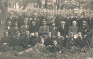 """Jurbarko """"Saulės"""" progimnazijos pedagogai ir moksleiviai. 2-oje eilėje sėdi iš kairės pedagogai: 3-ias Juozas Giedraitis, 4-as kapelionas kun. Povilas Šidlauskas, 5-as dir. Antanas Giedraitis, 6-a Ona Geniušienė, 7-as Antanas Šarkauskas, 8-as Albertas Šileris. Apie 1923 m. Nuotrauka iš Kristupo Šidlausko asmeninio archyvo"""