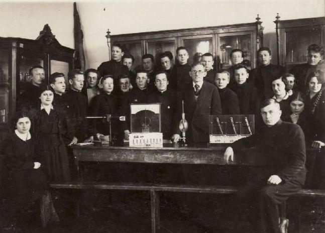 Vienas iš aktyvių verslininkų Venantas Morkūnas (centre) su Panevėžio valstybinės gimnazijos moksleiviais. XX a. 4 deš. Nuotrauka iš Panevėžio kraštotyros muziejaus rinkinių