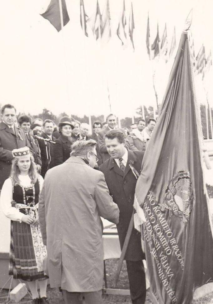 """Panevėžio rajono """"Tiesos"""" kolūkio pirmininkui, LSSR nusipelniusiam žemės ūkio darbuotojui, socialistinio darbo didvyriui, SSRS AT deputatui Albertui Meilui (kairėje) įteikiama raudonoji vėliava"""