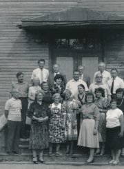 Grupė buvusių Krekenavos vidurinės mokyklos moksleivių prie senosios mokyklos pastato. Viršutinėje eilėje iš kairės 2-as: Č. G. Cemnolonskis. Krekenava (Panevėžio r.). Apie 1990 m. Panevėžio apskrities Gabrielės Petkevičaitės-Bitės viešoji biblioteka, Česio Gedimino Cemnolonskio fondas F105